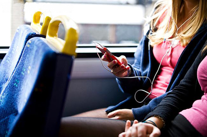 A teenage girl sitting on a bus, listening to music